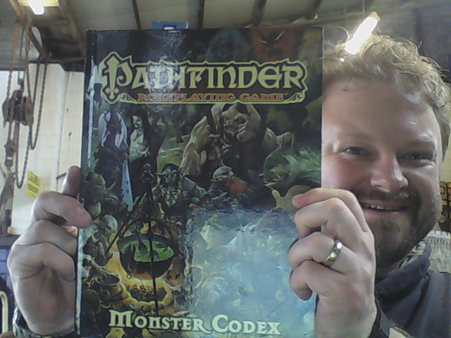 Monster Codex book held by Mark Knights