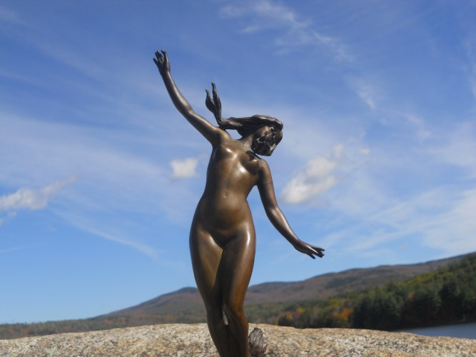 Bronze statue of naked female muse running free